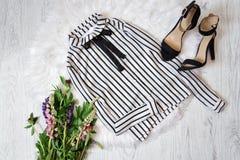 Vit randig blus och svarta skor på vit päls, en bukett av blommor trendigt begrepp Royaltyfria Foton