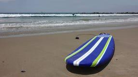 Vit randig surfingbräda för blått och på stranden Arkivbilder
