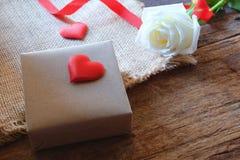 Vit ros och en gåvaask på trätabellen Gåva för vänbegrepp arkivbild