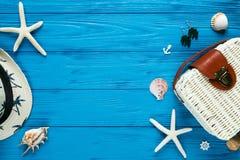 Vit rottingpåse, sugrörhatt på blå bakgrund moderiktig påse för bambu, sjöstjärna, skal Sommarmodelägenheten lägger, semestrar, r arkivbild