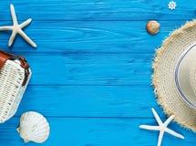 Vit rottingpåse, sugrörhatt på blå bakgrund moderiktig påse för bambu, sjöstjärna, skal Sommarmodelägenheten lägger, semestrar, r royaltyfria bilder