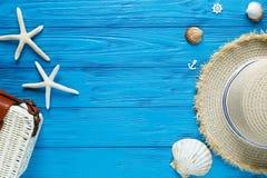 Vit rottingpåse, sugrörhatt på blå bakgrund moderiktig påse för bambu, sjöstjärna, skal Sommarmodelägenheten lägger, semestrar, r arkivfoto