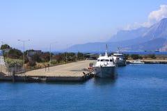 Vit sänder på pir i liten port, blå himmel och berg i bakgrund, Turkiet Royaltyfri Foto