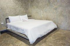 Vit säng med grå färgcementväggen Royaltyfria Foton