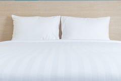 Vit sängkläderark och kudde i hotellrum arkivfoto
