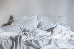 Vit sängkläderark och kudde, smutsigt sängbegrepp royaltyfri fotografi