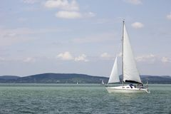 Vit segelbåt med härligt landskap royaltyfria foton