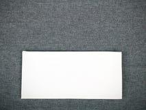 Vit servett på en grå bordduk royaltyfri foto
