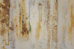 Vit skalande metallvägg med skrapor och fläckar av brun rost och grön målarfärg Textur för grov yttersida arkivbild
