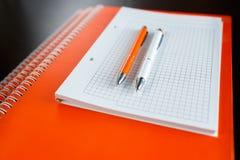 Vit sketchbook och orange anteckningsböcker som ligger på en trätabell för mörk brunt med pennor för en apelsin och vit Fotografering för Bildbyråer