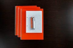 Vit sketchbook och orange anteckningsböcker som ligger på en trätabell för mörk brunt med pennor för en apelsin och vit Royaltyfri Foto