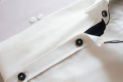 Vit skjorta med den svarta kragen och knappar Royaltyfri Bild