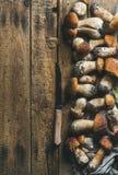 Vit skogchampinjoner och kniv på lantlig träbakgrund Royaltyfri Fotografi