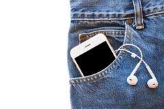 Vit smartphone i din fick- jeans med hörluren på isolerad bakgrund Arkivfoto