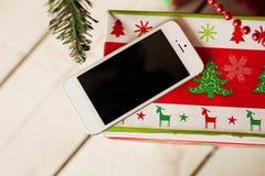 Vit smartphone med julträdet i bakgrund Arkivfoto