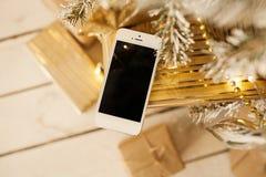 Vit smartphone med julträdet i bakgrund Royaltyfri Fotografi