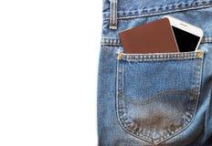 Vit smartphone och pass- eller mellanrumsanmärkningsbok i din fick- jeans på isolerad bakgrund Arkivfoto