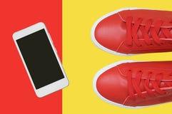 Vit smartphone och röda gymnastikskor arkivbild