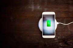 Vit smartphone som laddar på ett laddande block Arkivfoton