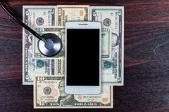 Vit smartphone tillsammans med amerikanska dollarräkningar och en stetoskop arkivfoto
