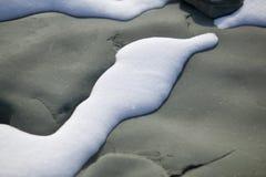 Vit snö och svart rock.JH Arkivfoton