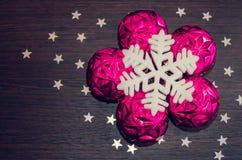 Vit snöflinga och magentafärgade xmas-struntsaker på brun träbakgrund med stjärnor Royaltyfria Bilder