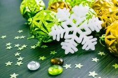 Vit snöflinga på bakgrund av gröna och guld- xmas-struntsaker Arkivbild