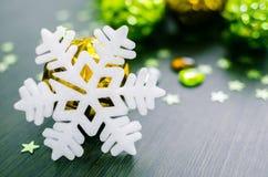 Vit snöflinga på bakgrund av guld och gröna xmas-struntsaker Royaltyfria Bilder