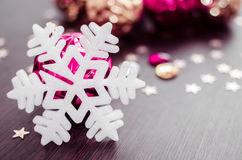 Vit snöflinga på bakgrund av magentafärgade och guld- xmas-struntsaker Arkivfoto