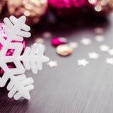 Vit snöflinga på bakgrund av magentafärgade och guld- xmas-struntsaker Arkivfoton