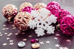 Vit snöflinga på bakgrund av magentafärgade och guld- xmas-struntsaker Royaltyfri Foto