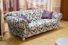 Vit soffa med den svarta modellen Fotografering för Bildbyråer