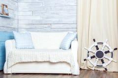 Vit soffa med ett styrninghjul Arkivbild