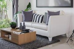 Vit soffa med trätabellen i modern vardagsrum fotografering för bildbyråer