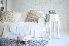 Vit soffa och nightstand med omställningkalendern i en stilfull vardagsrum royaltyfria bilder