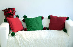 Vit soffa, tre kuddar, en blomkruka Fotografering för Bildbyråer