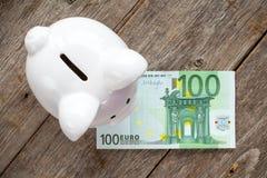 Vit spargris med euro 100 Royaltyfri Foto