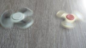 Vit spinnaresnurr för hand två på gråa bakgrunds- eller rastlös människaspinnare stock video