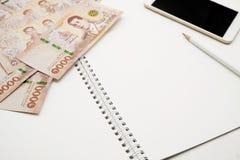 Vit spiralanteckningsbok för mellanrum med den vita blyertspennan, mobiltelefonen och högen av nya 1000 sedlar för thailändsk bah royaltyfri foto