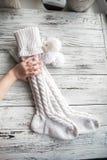 Vit stack sockor, handgjorda sockor på bakgrund Sockor för håll för en hand för barn` s Textur av stucken saker royaltyfri foto