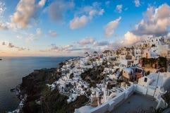 Vit stad på en lutning av en kulle på solnedgången, Oia, Santorini, Greec Royaltyfri Bild
