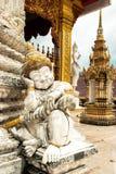 Vit staty med den guld- huvudbonaden Arkivfoton