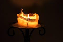 Vit stearinljus med flamman och det smältande vaxet på en järnljusstake a Arkivfoto