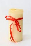 Vit stearinljus med röda bandferier Arkivbild