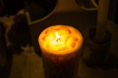 Vit stearinljus mot mörk bakgrund - fotografi av en tänd vit stearinljus mot en vanlig mörk bakgrund Överflöd av rum Royaltyfria Bilder