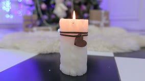 Vit stearinljus på bakgrunden av julgranen stock video