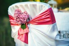 Vit stol dekorerade med rosa vanliga hortensior som var utomhus- för gifta sig eller annan händelse Royaltyfri Fotografi