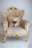 Vit stol med blommabouqet arkivfoto