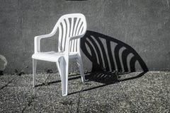 Vit stol med en skugga arkivfoto