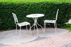Vit stol och vittabell i trädgården royaltyfria bilder